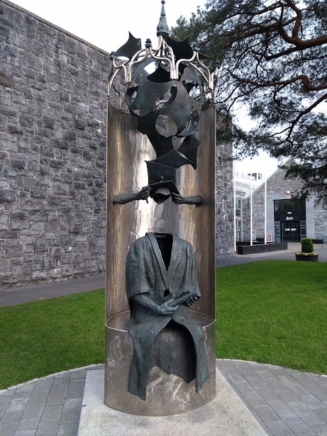 A sculpture of an empty cap and gown holding a scroll