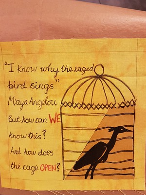 Completed bird sample quilt block with appliqued bird, drawn cage and text