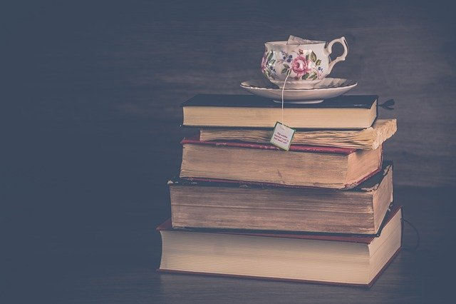 Pile of books with cup of tea on top